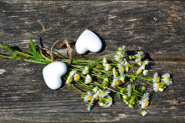 bouquet of daisies lying on the board. next to two white hearts