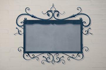 blue signboard hanging on white brick wall