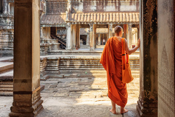Wall Mural - Buddhist monk exploring courtyards of Angkor Wat, Siem Reap