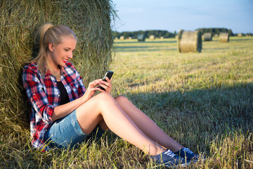 beautiful blonde woman sitting near haystack in field with mobil