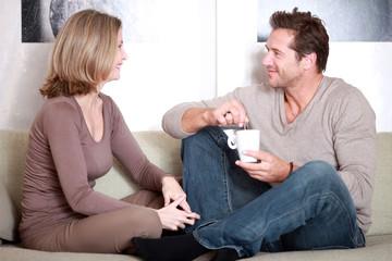 Mann und Frau auf der Couch mit einer Tasse