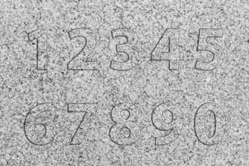 Zahlen aus Granitstein auf einer Granitsteinplatte