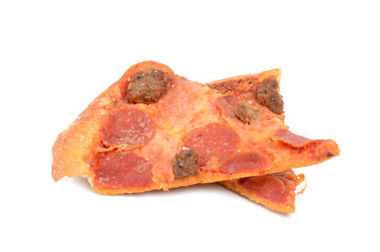 two slices leftover pizza on white background