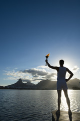 Silhouette of an athlete standing with sport torch against the the setting sun of the Rio de Janeiro Brazil skyline at Lagoa lagoon