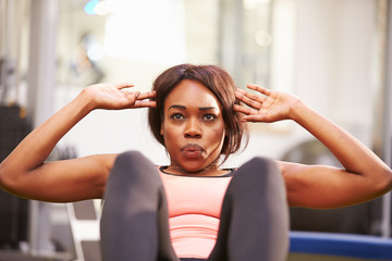 Young woman doing crunches in a gym, close up