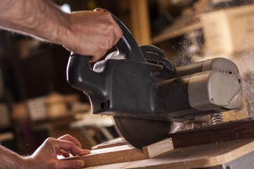 carpenter cutting a plank with compound mitre saw