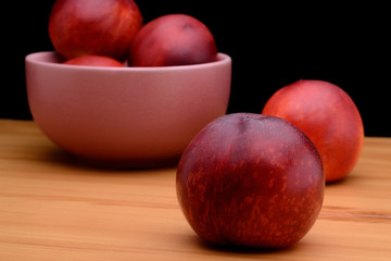 Ripe nectarines are in a plate on a table on a black background