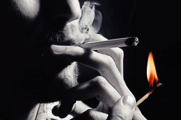 Men's hand lights a cigarette with a match