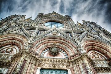 Santa Maria Assunta facade in Siena under a dramatic sky