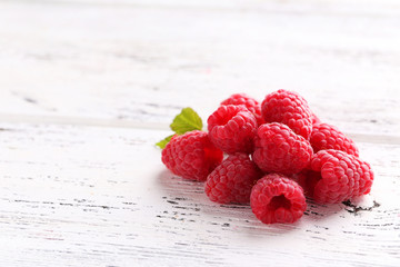 Red raspberries on white wooden background