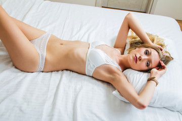 Sexy girl in white lace underwear lying on the bed