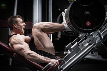 Man in gym training at leg press