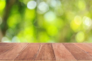 Top wooden table with sunny abstract green nature background, bl