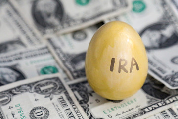IRA retirement saving golden egg on cash