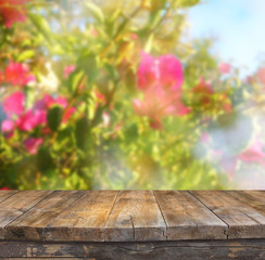 wood board table in front of summer landscape of flower bloom