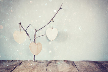 abstract image of hanging wooden hearts. glitter overlay