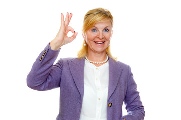 Portrait of Happy smiling old senior woman 60-65 years with white teeth, shows gesture ok. In suit with big blue eyes, isolated on white background, Positive human emotion, facial expression