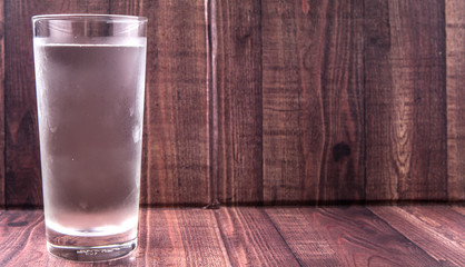 A glass of water over wooden background