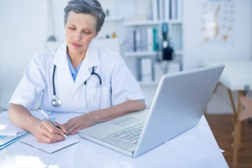 Female doctor writing on paper