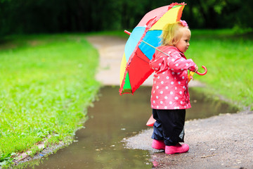 little girl with umbrella in raincoat and boots outdoor