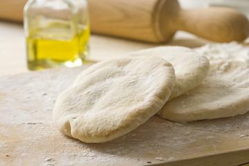 Raw pita bread on on a wooden cutting board.