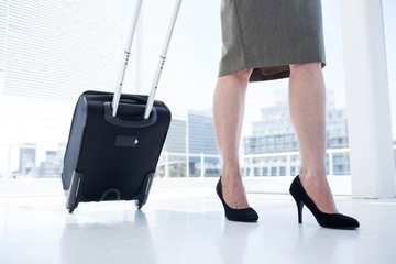 Businesswoman pulling her suitcase in the office