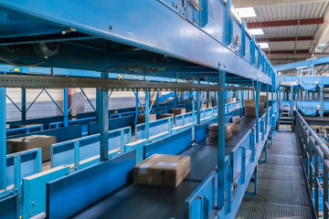 Parcels on conveyors with blurred industrial background