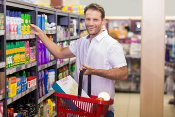 Portrait of a smiling handsome taking a product in shelf