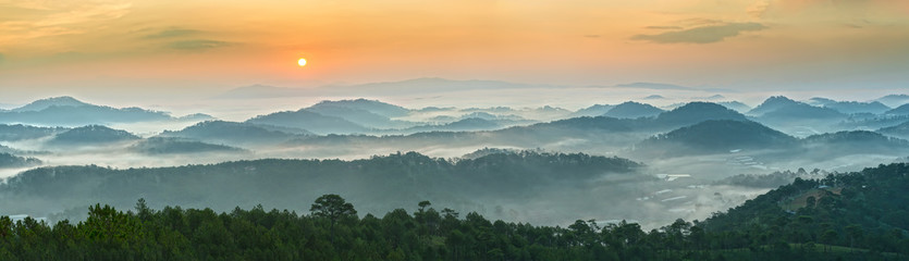 Sunrise over the panoramic mountains of Dalat  with his sun rise on the hill waxing pine soon covered with clouds and fog do to honor the beauty highland Da Lat