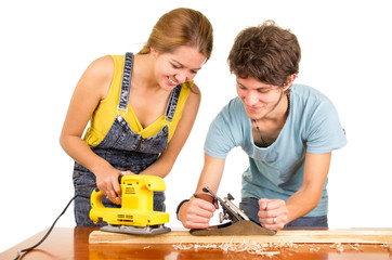 Couple standing by working desk as woman uses electric sander