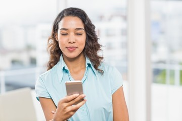 Happy young creative businesswoman texting