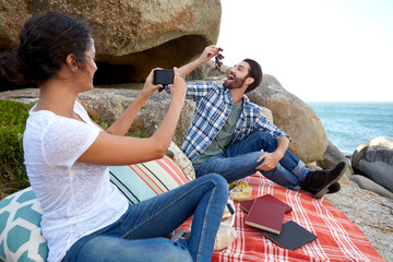 Happy couple taking pictures during a relaxed picnic on the rock