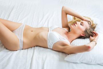 Sexy girl in white lace underwear lying on the bed, emotive, closed eyes
