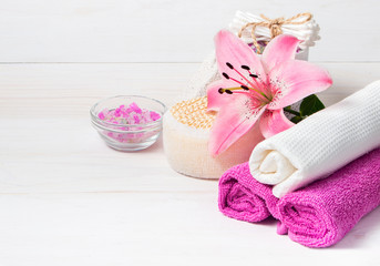 Spa concept. Pink lily flower,sea salt,towels and objects for sp
