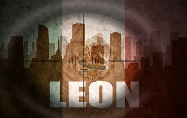 sniper scope aimed at the abstract silhouette of the city with text Leon at the vintage mexican flag