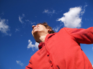 Happy mature woman against blue sky