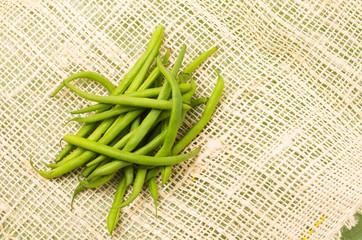 Bunch of fresh green peas placed on a rustic hemp fabric
