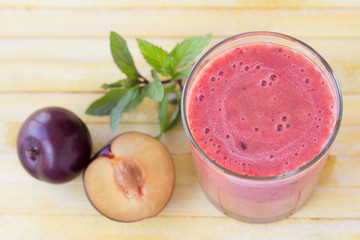 Plum smoothie with fresh plums and mint on yellow toned wooden surface
