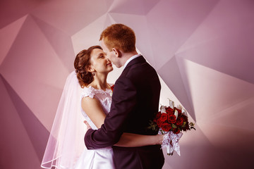 Portrait of beautiful young wedding couple kissing at pink wall