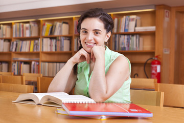 Cute female student studying at the university library