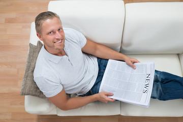 Man On Sofa With Newspaper