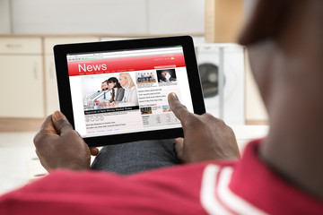 African Man Reading News On Digital Tablet