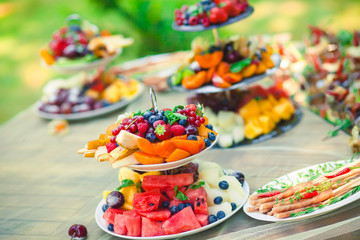 Beautifully decorated catering banquet table with different food snacks and appetizers with sandwich, caviar, fresh fruits on corporate birthday party event or wedding celebration