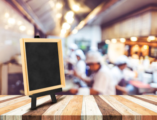 Blackboard menu with easel on wooden table with blur open kitche