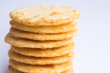 A stack of cheesy rice crackers on a white background.