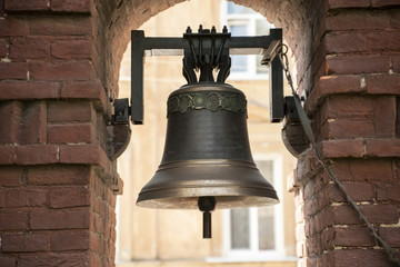 The old bronze bell near the brick wall