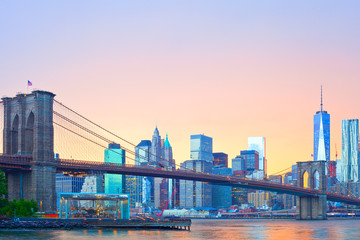 New York City skyline, Manhattan downtown panorama with famous landmark Brooklyn Bridge at colorful sunset