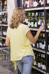 Back view of a blonde woman looking at a wine bottle