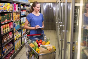 Pretty woman looking at product on freezer