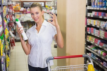 woman taking cleaning product in the shelf of aisle